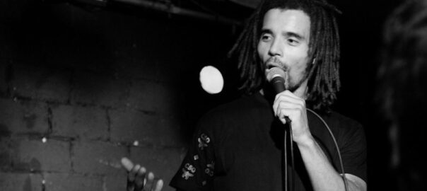 Black and white photograph of Akala performing on a darkened stage
