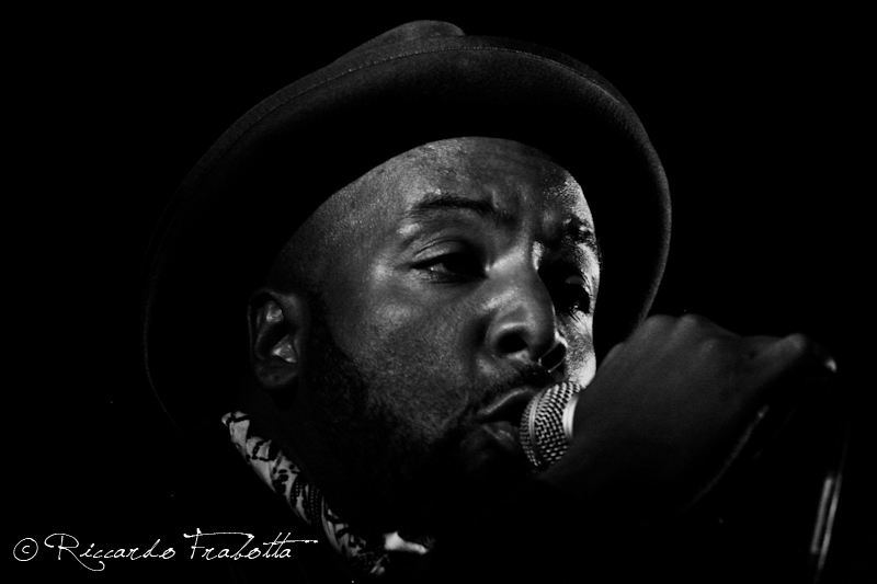 A black and white portrait of Roger Robinson performing on-stage as part of King Midas Sound